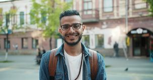 Slow motion of Arabian man standing outdoors with serious face then smiling. Slow motion portrait of attractive Arabian man in stylish clothing standing outdoors stock video