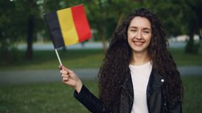 Slow motion portrait of attractive girl world traveller waving Belgian flag, looking at camera and smiling standing in. Slow motion portrait of attractive girl stock footage