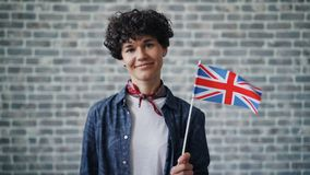 Slow motion portrait of attractive lady holding British flag on brick background. Slow motion portrait of attractive lady holding British flag on brick wall stock video footage