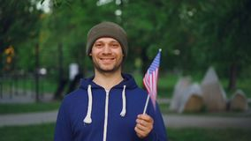 Slow motion portrait of bearded American guy proud citizen waving official US flag and looking at camera with glad smile. People, world countries and stock footage