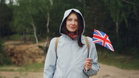 Slow motion portrait of charming Englishwoman holding flag of the Great Britain, smiling and looking at camera. Slow motion portrait of charming Englishwoman stock video