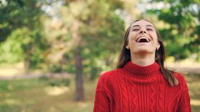 Slow motion portrait of cheerful girl in warm sweater standing in the park with glad smile, laughing and looking at. Slow motion portrait of attractive cheerful stock video footage