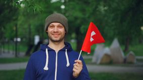 Slow motion portrait of cheerful guy world traveller in casual clothes holding Swiss flag, looking at camera with glad. Slow motion portrait of cheerful guy stock video footage