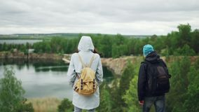 Slow motion portrait of cheerful world travellers girl and guy with backpacks walking to the edge of high rock and. Watching beautiful landscape river and woods stock footage
