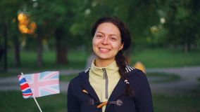 Slow motion portrait of cheerful young lady in casual clothes waving national flag of the United Kingdom, smiling and. Looking at camera with green park in stock video