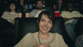 Slow motion of cheerful woman laughing watching film in cinema holding drink stock footage