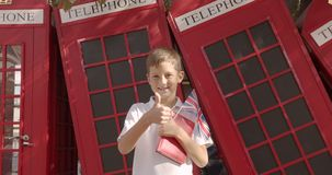 Slow motion portrait of cute boy standing outdoors alone smiling looking at camera. On the background English red. Telephone booths. Travelling concept stock footage