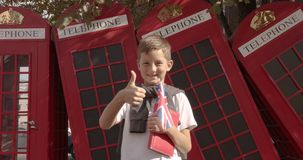 Slow motion portrait of cute boy standing outdoors alone smiling looking at camera. On the background English red. Telephone booths. Travelling concept stock video