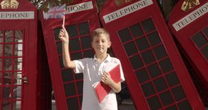 Slow motion portrait of cute boy waving British flag standing outdoors alone smiling looking at camera. On the. Background English red telephone booths stock video