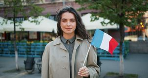 Slow motion portrait of cute French girl standing outdoors with flag of France. Smiling looking at camera. Patriotism, young people and travelling concept stock footage