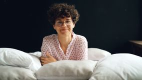 Slow motion portrait f attractive curly-headed woman in glasses and casual clothing looking at camera and smiling lying stock video