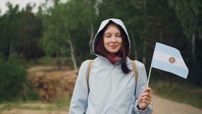 Slow motion portrait of female world traveller holding Argentinian flag flying in the wind, smiling and looking at. Slow motion portrait of pretty female world stock footage