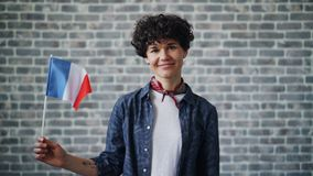 Slow motion portrait of French lady holding official flag of France and smiling. Looking at camera standing on brick wall background. People and countries stock footage