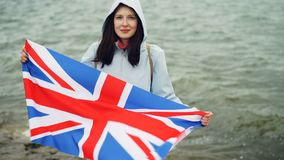Slow motion portrait of glad tourist visiting Great Britain holding British national flag and smiling standing on sea. Shore with beautiful nature visible stock video footage