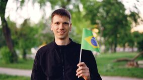 Slow motion portrait of glad traveller young man holding Brazilian flag and smiling looking at camera. National symbol. Slow motion portrait of glad traveller stock footage
