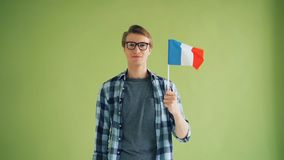 Slow motion of good-looking guy with French flag looking at camera and smiling. Slow motion portrait of good-looking guy with French flag looking at camera and stock footage