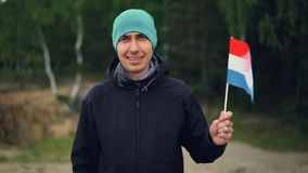 Slow motion portrait of handsome guy in sports clothes waving flag of the Netherlands, smiling and looking at camera. Slow motion portrait of handsome guy in stock video footage