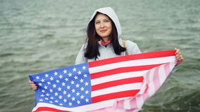 Slow motion portrait of happy American girl holding United States flag and moving it standing on the sea coast with. Waves visible. Nationality, people and stock video footage