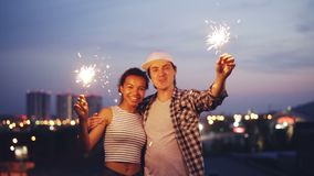 Slow motion portrait of happy multiracial couple African American woman and Caucasian man holding bengal lights, looking