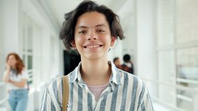 Slow motion portrait of happy teenager laughing in school hall looking at camera. Standing alone in hallway with joyful face. Youth and education concept stock footage