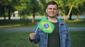 Slow motion portrait of happy world traveller emotional young man waving Brazlian flag after visiting Latin American. Country. People, adventure and tourism stock footage