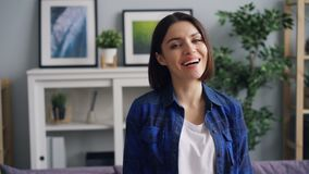 Slow motion portrait of happy young lady smiling and laughing having fun at home