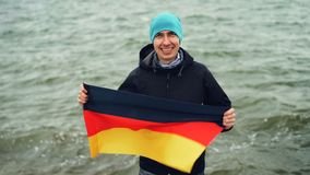 Slow motion portrait of joyful German sports fan holding flag of Germany and smiling while standing near the lake and