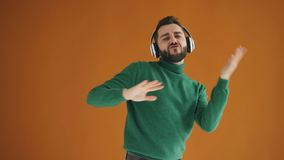 Slow motion portrait of joyful guy dancing listening to music in headphones stock footage