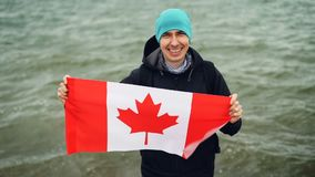 Slow motion portrait of joyful young man traveller holding Canadian flag in hands and looking at camera with glad smile. Slow motion portrait of joyful young man stock footage