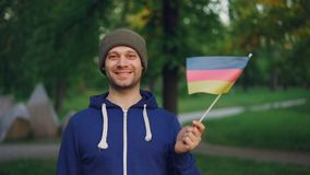 Slow motion portrait of male German sportsman handsome bearded man waving flag of Germany and smiling standing in city