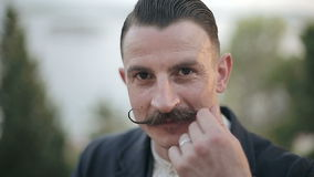 SLOW MOTION: Portrait of a man with a mustache that curls mustache hand stock video