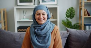 Slow motion of Middle Eastern woman in hijab looking at camera smiling at home. Slow motion portrait of Middle Eastern woman in hijab looking at camera and stock video footage
