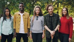 Slow motion portrait of multi-ethnic group of friends happy young people standing in the park together smiling and