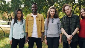 Slow motion portrait of multiracial group of students girls and guys standing outdoors together and looking at camera stock video