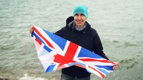 Slow motion portrait of patriotic Englishman holding flag of Great Britain standing on sea coast and smiling happily