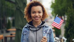 Slow motion portrait of pretty African American girl teenager looking at camera and holding US flag standing outside in. Modern city. Tourism and happy people stock footage