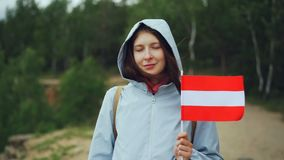 Slow motion portrait of pretty Austrian lady proud citizen holding flag of Latvia, smiling and looking at camera. Slow motion portrait of pretty Austrian lady stock footage