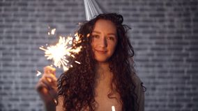 Slow motion of girl in party hat holding sparkler smiling on brick background. Slow motion portrait of pretty girl in party hat holding sparkler smiling on brick stock video footage