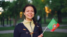 Slow motion portrait of pretty Portugese woman holding official flag of Portugal, smiling and looking at camera. Active