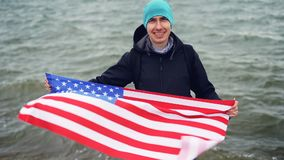 Slow motion portrait of proud American man holding US flag celebrating Independence day near the sea looking at camera stock video