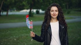 Slow motion portrait of world traveller happy girl waving Norwegian flag, looking at camera and smiling. Beautiful park. Slow motion portrait of proud world stock video