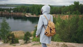 Slow motion portrait of young woman tourist with backpack walking to the edge of cliff with beautiful view of lake and. Slow motion portrait of slim young woman stock video footage