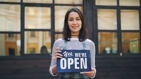 Slow motion portrait of smiling young woman entrepreneur holding we are open sign standing outdoors in front of her new
