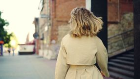 Slow motion portrait of smiling young woman in trendy coat walking in the street, turning to camera and looking at stock video