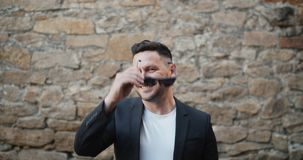 Slow motion portrait of stylish bearded guy taking off sunglasses smiling. Outdoors standing alone with brick wall in background. People and identity concept stock video footage