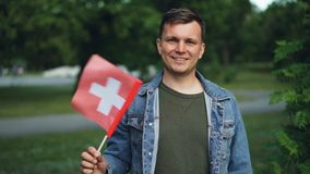 Slow motion portrait of Swiss sports fan smiling, waving flag of Switzerland and looking at camera with green trees and