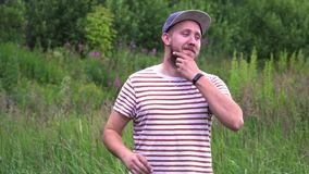 Slow motion portrait of young bearded funny man with cap OK hand gesture. stock footage
