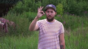 Slow motion portrait of young bearded funny man with cap show OK hand. stock footage