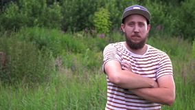 Slow motion portrait of young bearded funny man with cap turn around cross arms. stock footage