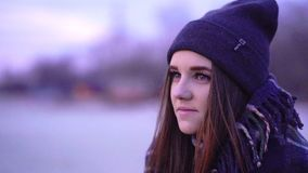 SLOW MOTION: Portrait of a young beautiful frozen girl in a sports hat and a warm plaid in the morning. Before the sunrise of the autumn sun stock video footage